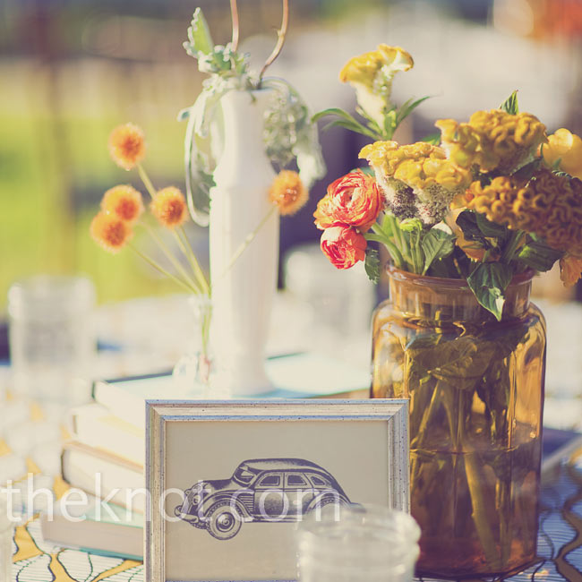 Stacked vintage books, a few antique vases, and clusters of orange roses, craspedia and stock made up each retro centerpiece.