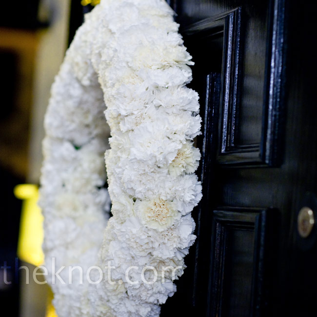 A wreath of fresh white carnations hung on Katie's parents' front door.