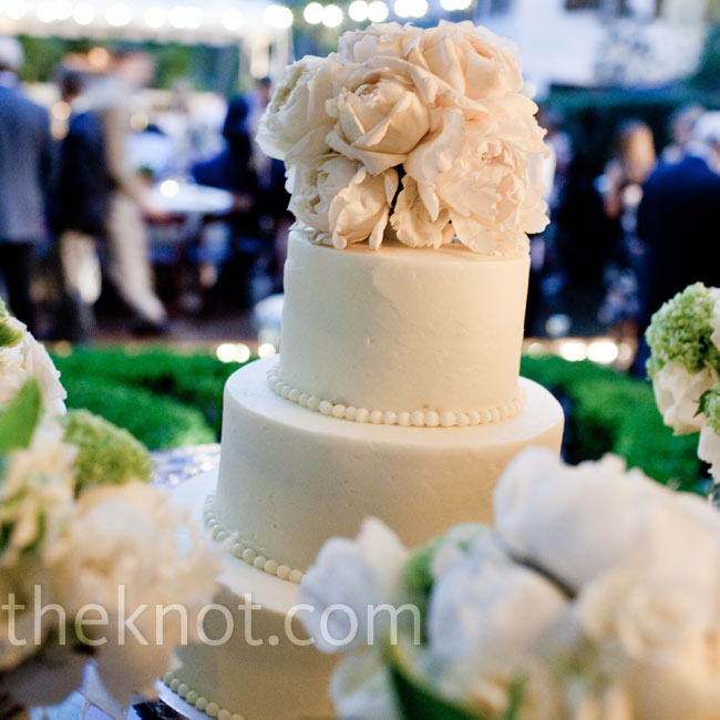 The simple buttercream cake was topped off with garden roses and displayed on a round mosaic table.