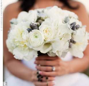 Francesca's wintry bouquet was made up of peonies, hydrangeas, ranunculus and roses, and was accented with pine cones.