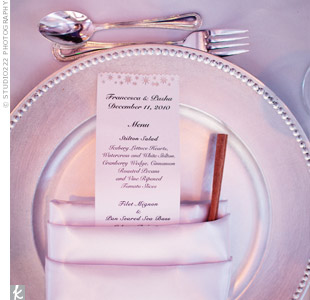 Each place setting included a silver charger, a white satin napkin, a shimmery menu card and a cinnamon stick.