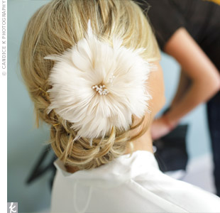 An oversize feather flower finished off Amandas low bun.