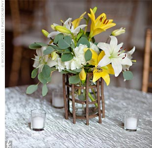 Mason jars filled with white and yellow lilies and hydrangeas were set inside wooden baskets.