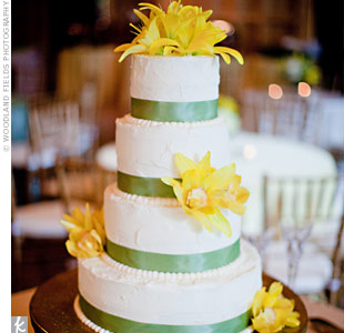 Green grosgrain ribbon and yellow lilies decorated this buttercream cake.