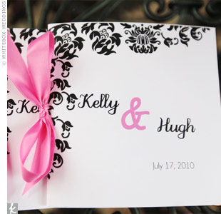 Fuchsia ribbon bound together the black-and-white damask-patterned ceremony programs.