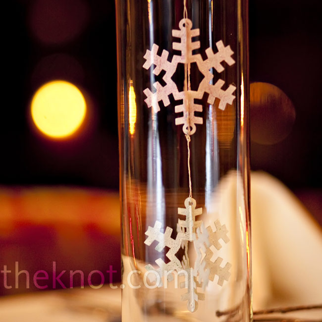 In addition to flower arrangements, the couple used large cylinder vases displaying suspended white snowflake ornaments inside.