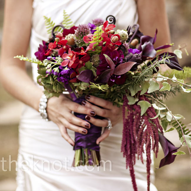 Flowers like dahlias, roses, orchids and burgundy amaranth in autumn-inspired colors made up Josie's cascading bouquet.