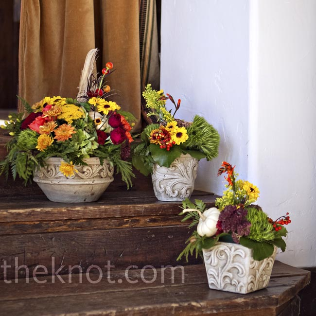 Autumn-colored mums, roses and daisies combined with heavy greenery, acorns and berries were displayed in pots of varying size.