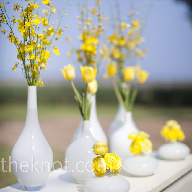 A distressed table, topped with white vases of different heights and filled with an array of yellow flowers, sat near the altar.