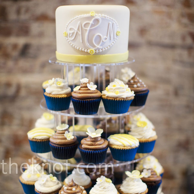 The bride and groom cut into a monogrammed white and yellow cake, which topped a tower of cupcakes in a variety of flavors.