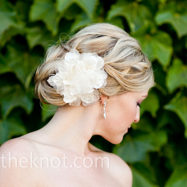 Beth wore her hair in a low bun with a silk flower set on one side.