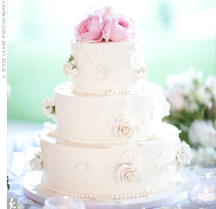 Handmade sugar flowers and rose petals decorated the couples buttercream cake, which was topped with fresh, soft-pink roses.