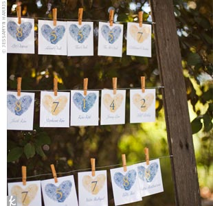The escort cards (stamped with fingerprint hearts) hung from clothespins inside an empty wooden frame.