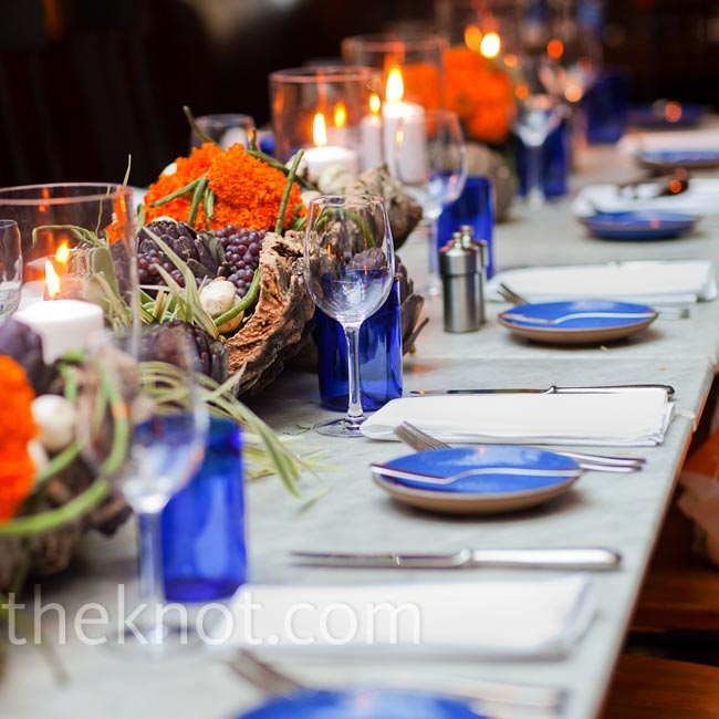 Rustic centerpieces mixed with artichokes and berries were set into tree-trunk-like vessels and placed down the tables.