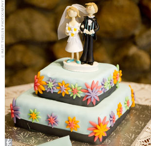 Karli and James cut into a two-tiered cake with multicolored fondant flowers and a wax figure bride and groom topper.