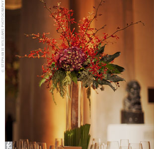 Tall, textured arrangements of hydrangeas, orchids, proteas, spider mums and berries, set in leaf-wrapped cylinder vases, topped some of the dinner tables.