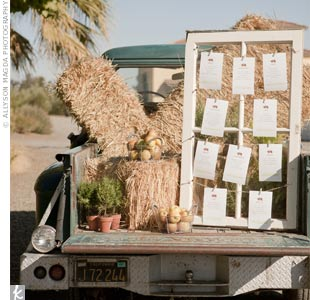 n keeping with the farm theme, table assignments hung from twine inside an old wooden window frame set on the bed of a truck filled with hay bales.