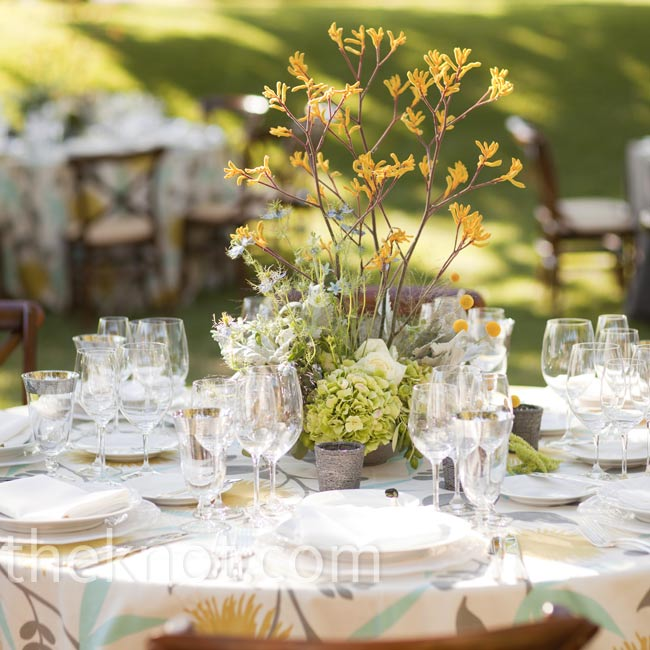 Eclectic arrangements of branches, kangaroo paws and herbs mirrored the wedding's farm setting.