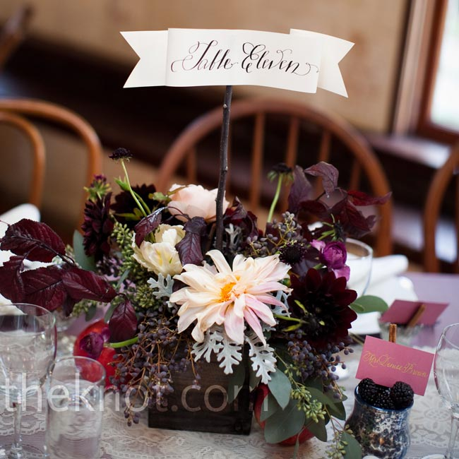 Floral arrangements of dahlias, herbs and berries topped the lace table runners.