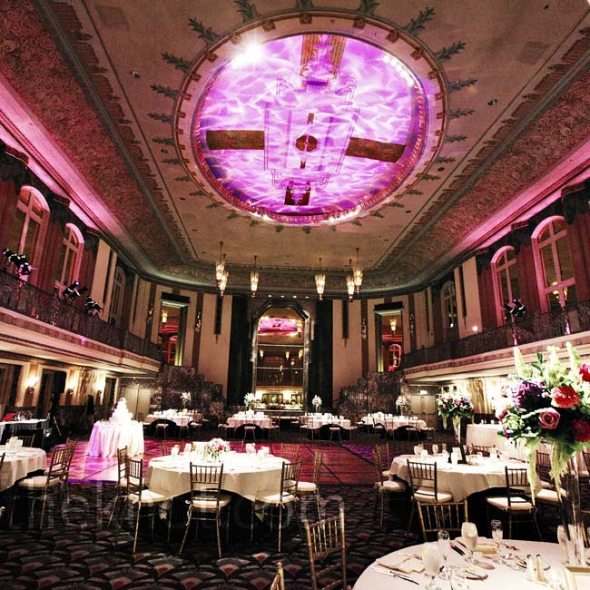The space had high ceilings, so the couple opted for both low and high florals. Purple lighting gave the room a romantic look.