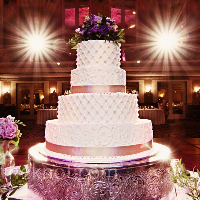 Alternating lattice-pearl and filigree patterns donned the tiers. The couple's florist created a topper of purple flowers.