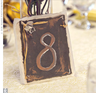 To carry the rustic vibe over into the tablescapes, the brides sister hand painted each table number on handmade paper.