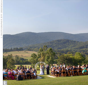 The couple stood beneath a vintage iron archway with the breathtaking Blue Ridge Mountains in the background.