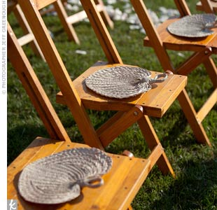 Hand-woven palm fans sat on each chair to help guests keep cool during the outdoor summer ceremony.