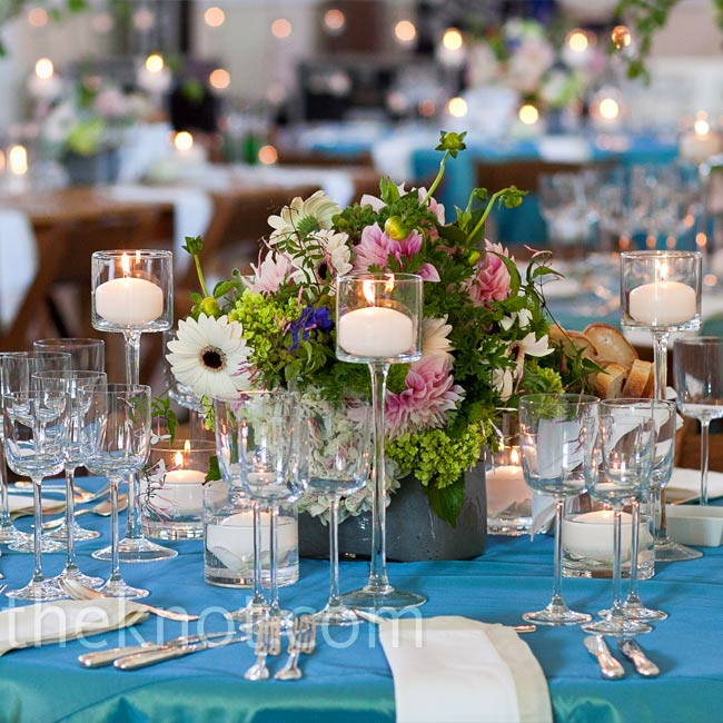 French blue topaz linens covered the smaller tables, which featured shorter centerpieces surrounded by glass pedestal candleholders, filled with rose petals and pillar candles.