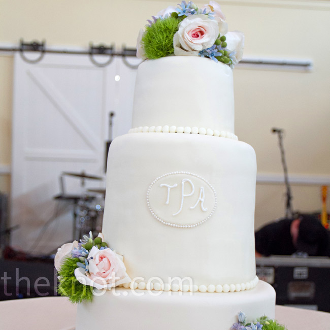 Iced pearls lined the bottom of each tier of the cream fondant covered cake, which was personalized with the couple's monogram.