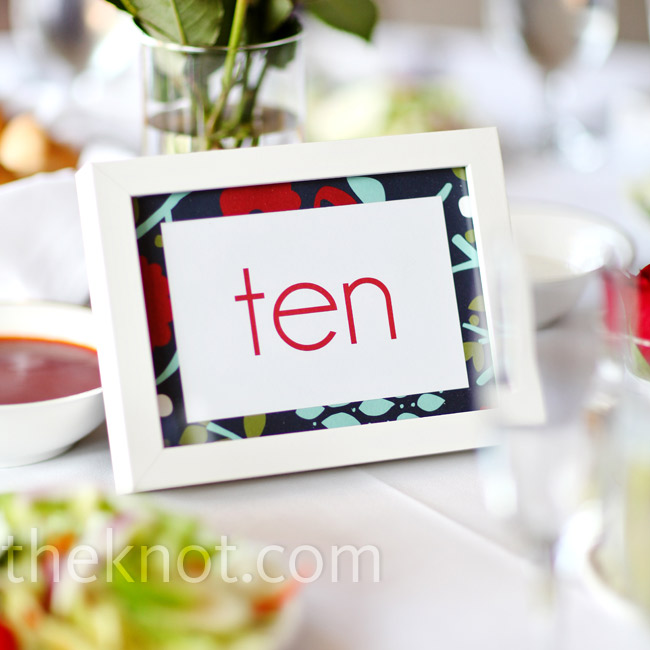 Holly used the same printed paper from the escort cards to matte the modern-font table numbers in red print and white frames.