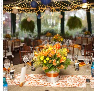 Tables were covered in burlap linens with orange damask-patterned runners. Bright orange and yellow blooms were arranged in silver-painted tomato cans for a fun and casual wildflower look.