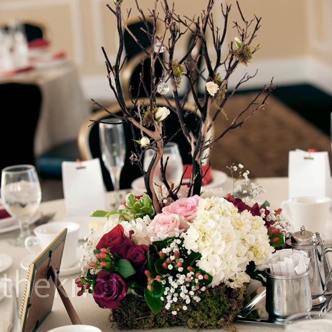 Low bunches of roses, hydrangeas and carnations made a romantic base for rustic manzanita branches.