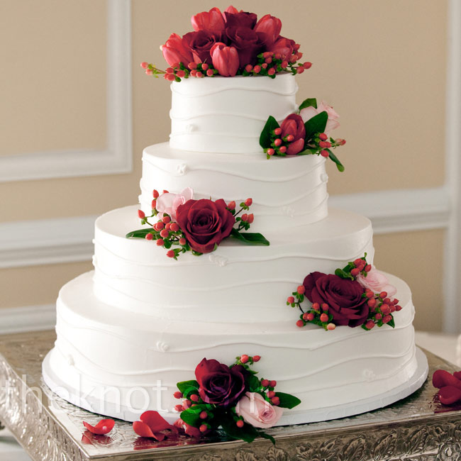 Fresh red roses and tulips decorated each tier of the buttercream cake.