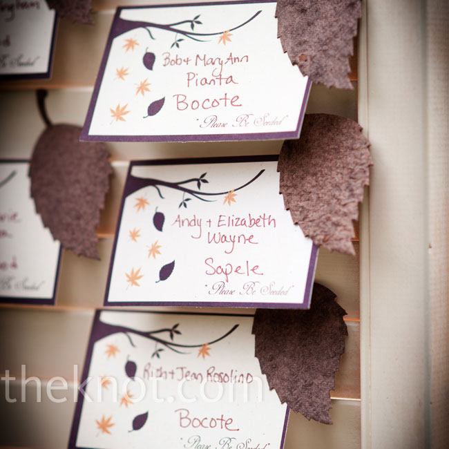 Escort cards with plantable wildflower seeds pressed into the shape of a leaf were displayed in the slats of an old wooden door.