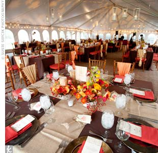 Dinner was served inside a heated tent decorated with orange uplighting. Guests sat at tables topped with brown and tan linens.