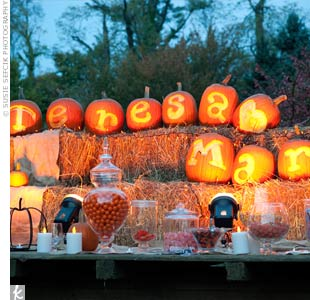 "The candy buffet outside the reception tent was decorated with lit-up pumpkins carved to spell out ""Teresa [heart] Mark."""