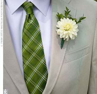 Mike paired his green-plaid tie with a simple white dahlia boutonniere.