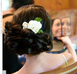 Susan wore her hair pulled to the side in a low, twisted bun. A silk flower tucked in at the top finished the look.