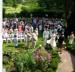 The couple exchanged vows on the grass, facing a garden at Crossed Keys Inn.