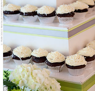 Chocolate cupcakes topped with white frosting and displayed on tiers decorated with green ribbon matched the wedding colors.