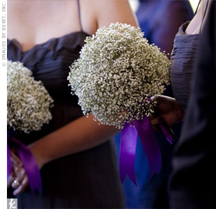 The bridesmaids carried big bouquets of baby's breath wrapped in purple ribbon.