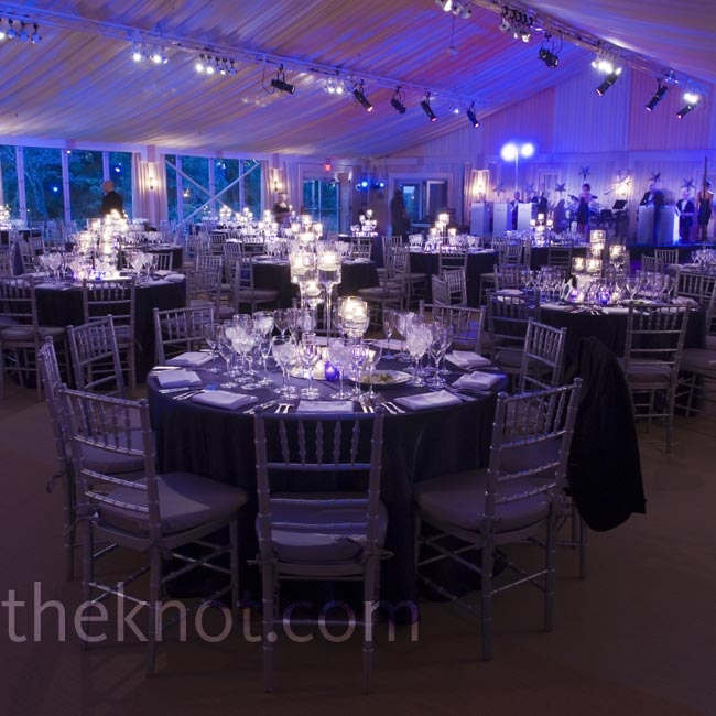 The tent was uplit with purple and blue lighting for a cool, romantic look, while minimalist centerpieces with floating candles (no flowers) topped the tables.