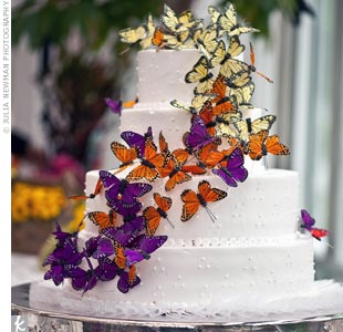 Orange, purple and yellow paper butterflies cascaded down the white tiers.