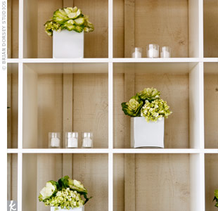 Divided shelves topped with candles and flowers spruced up the back bar at the reception.