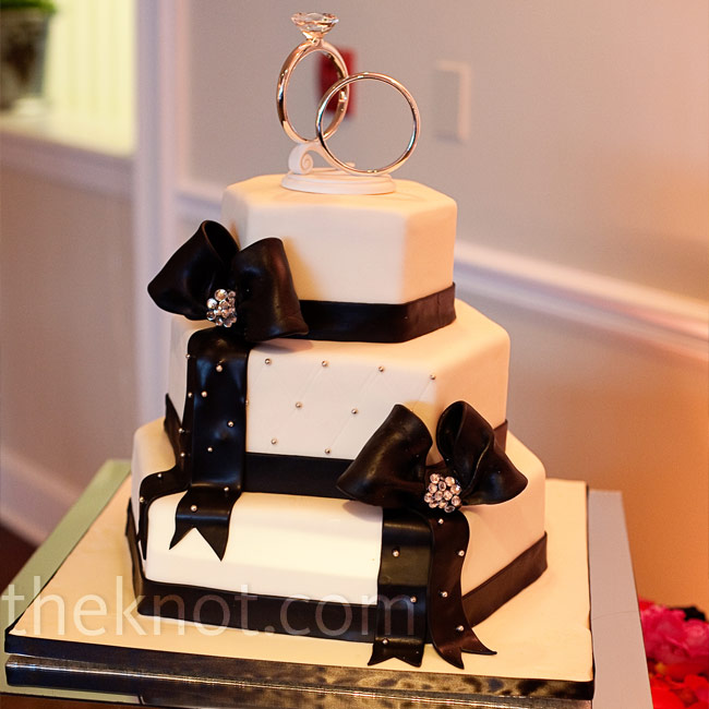 A hexagon-shaped cake was modern and unexpected, as was the topper of oversize rings. Bedazzled centers on the black bows were another sparkly touch.
