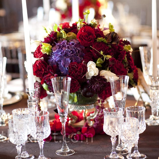 The arrangements included roses and other jewel-toned blooms, along with peacock feathers and ripe fruits like plums and pomegranates.