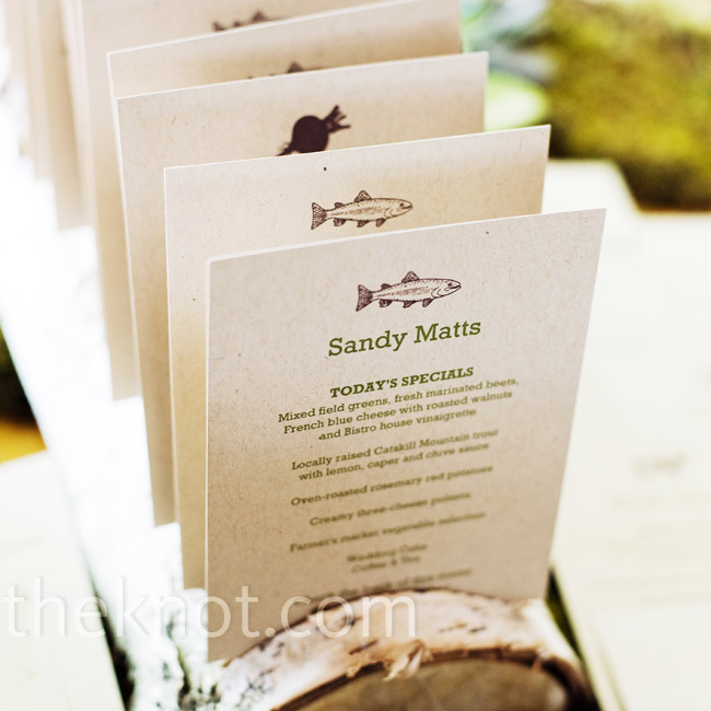 The couple had individual menu cards made for each guest. They stamped table numbers on the backs (instant escort cards) and then displayed them in a birch log.