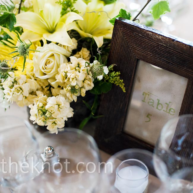 Low-key centerpieces of yellow roses and lilies rested next to the table numbers set in brown frames.
