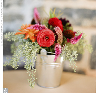 Mini metal buckets filled with ranunculus, dahlias and seeded eucalyptus topped the cocktail tables.
